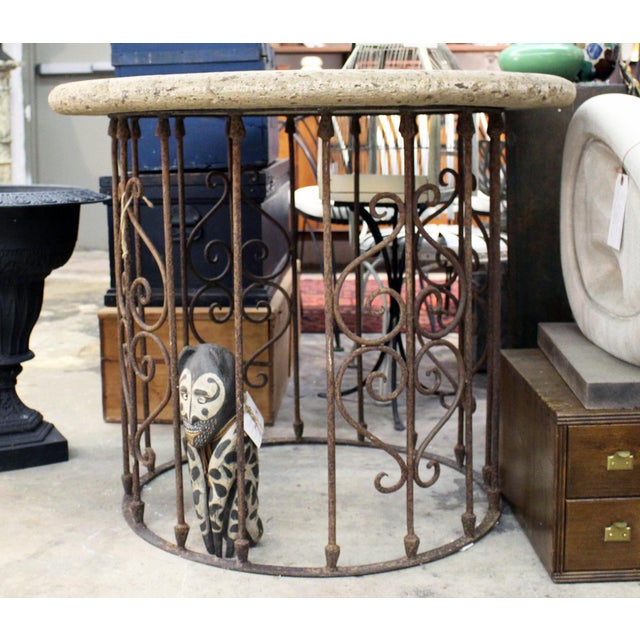 A thick weathered round coral table top resting on a circular classical inspired hearts and scrolls, rusted wrought iron...