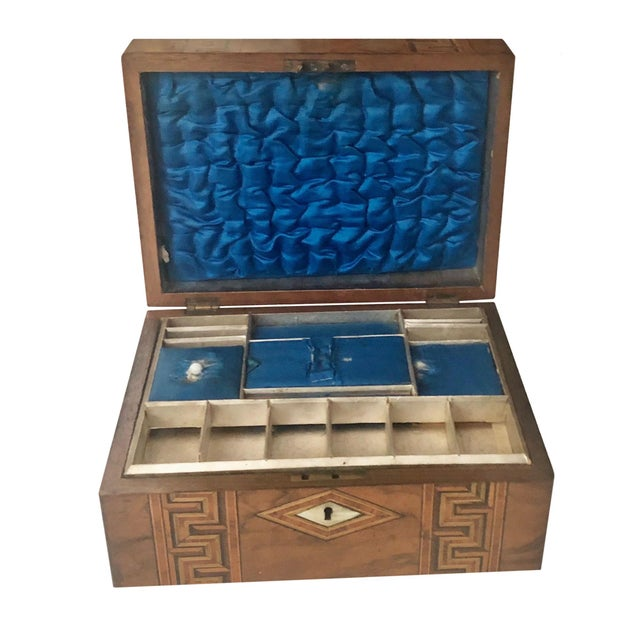 A turn of the century marquetry inlay French box with mother of pearl. Interior lid and tray with royal blue silk.