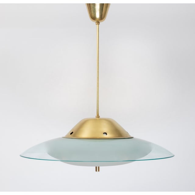 A graceful and spare chandelier by Max Ingrand for Fontana Arte, with a frosted glass bowl, a large curved crystal shade,...