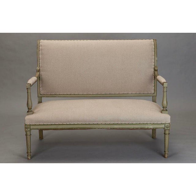 Circa 1900 Empire style carved and upholstered French settee. Antique green painted finish and newly upholstered in a...