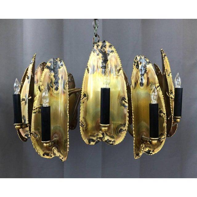 An impressive thirteen-light Brutalist brass chandelier by Tom Greene for The Feldman Company of Los Angeles. Torch-cut...