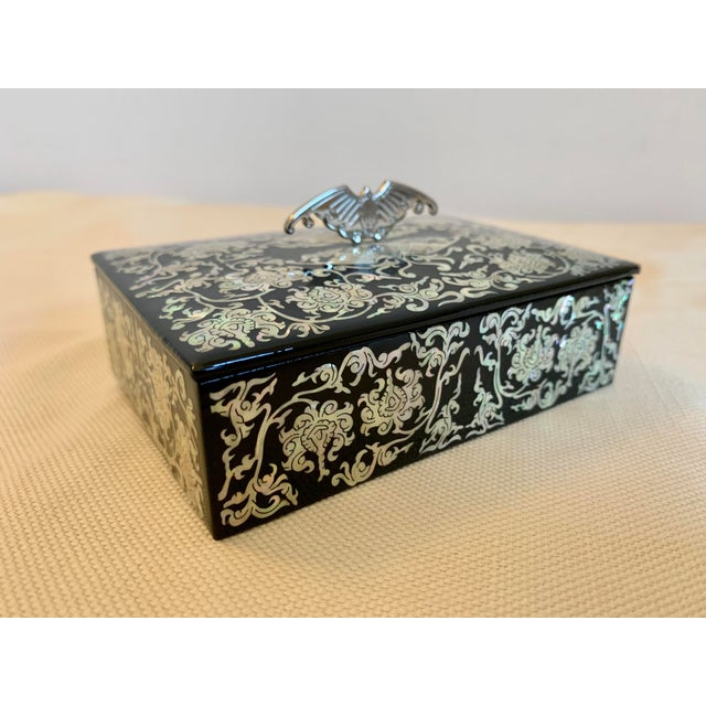 This expertly crafted lacquer box has a striking mother of pearl inlay pattern with a metal handle in the profile of a...