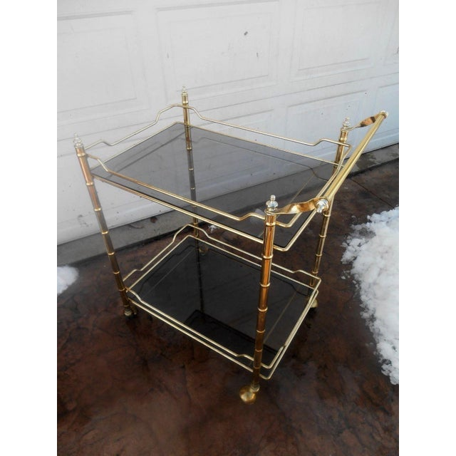 Vintage Mid Century Modern Faux Bamboo Shiny Brass Rolling Bar / Tea Cart. Wonderful two tier rolling tea / bar cart with...