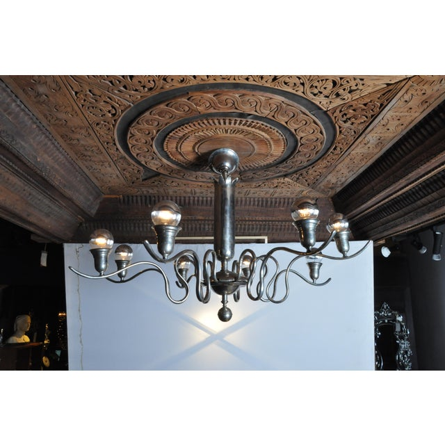 This graceful eight-light chandelier has fluid, ribbon like S-scroll arms that extend from a central column.