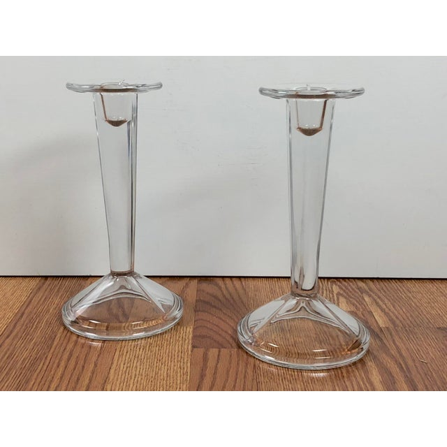 A pair of stately, solid clear glass Mid-Century, Art Deco style candle holders. Tall, Sleek and heavy in weight with a...