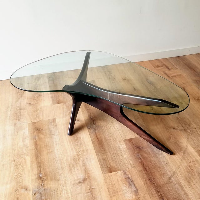 An unmarked Model 1465-T glass and walnut boomerang coffee table designed by Adrian Pearsall for Craft Associates. This...