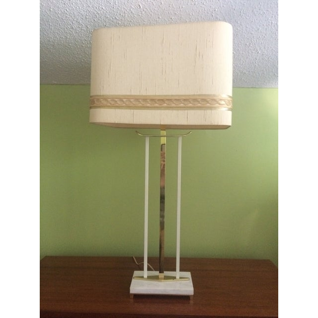 This sculptural Mid-Century table lamp is comprised of brass and white enamel and sits atop a handsome marble base. Its...