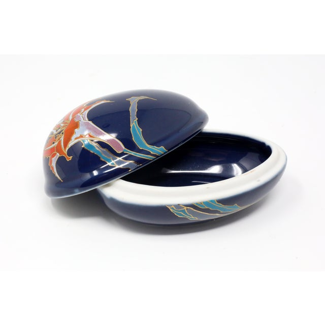 A vintage, ceramic box in the form of an egg, with deep blue glaze and a colorful image of a peruvian lily. Excellent...