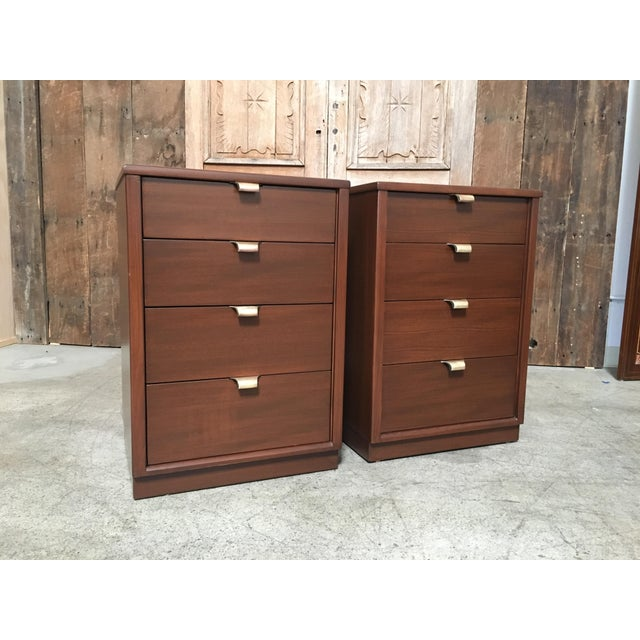 Great pair of precedent nightstands finished in a medium walnut with solid brass drawer pulls.