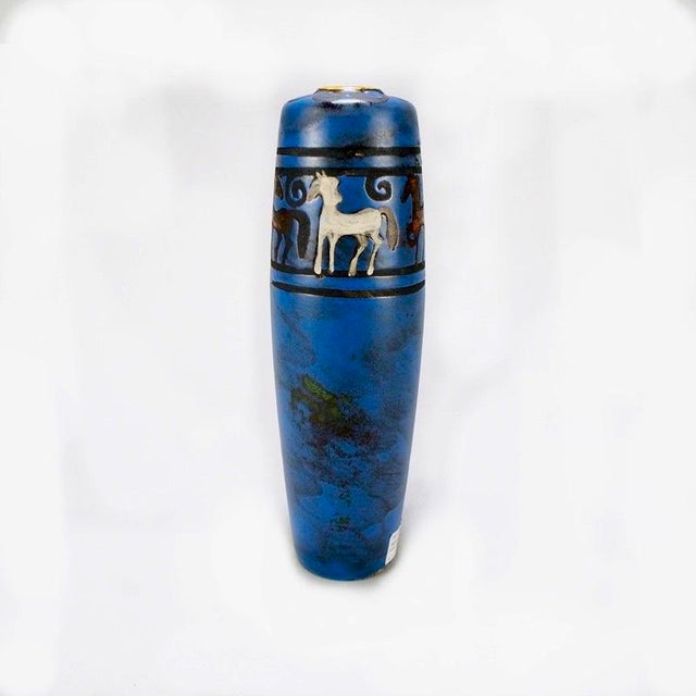 Circa 1970s hand made tall German ceramic vase in blue vase with band of stylized multi colored horses around vessel....