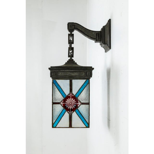 A four-sided, wall hanging, bronze lantern with leaded stained glass in white, blue, and deep red; with textured and cut...