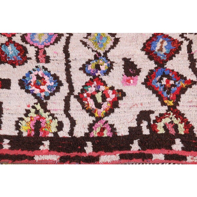 Originating from Morocco in the 1950s, this vintage mid-century Moroccan rug employs a distinguished transitional style...
