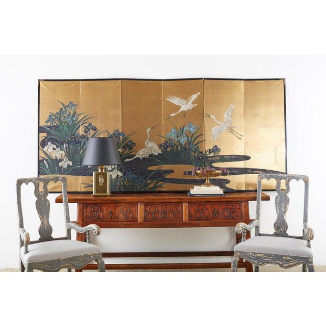 Captivating Japanese six-panel Meiji screen featuring five egrets or herons in a water landscape. Painted with vibrant...