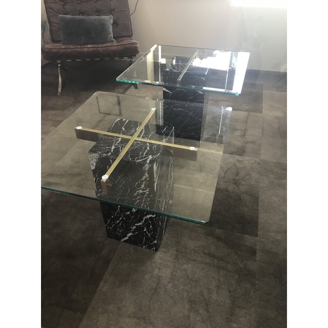Striking pair of Artedi side tables with dramatic Nero Marquina black marble bases and brass cross supports. Wear typical...