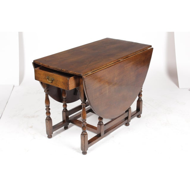 1920s English oak Jacobean-Style gate leg table featuring drop leaf sides, turned spool legs, single drawer and pull out...