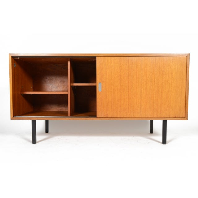 Low and sleek, this modern teak credenza by Robin Day features large sliding doors with unique carved pulls with aluminum...