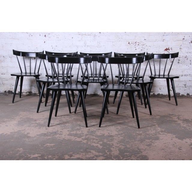 Offering a gorgeous set of ten ebonized mid-century modern spindle back dining chairs from the Planner Group line designed...