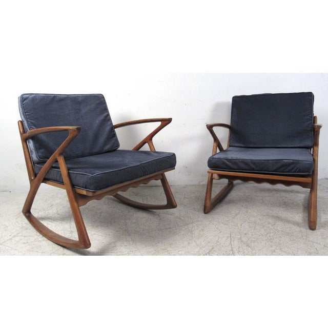 Two vintage-modern lounge chairs in the style of Poul Jensen, featuring beautifully sculpted Z frames, slatted backs, and...