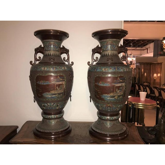 A Monumental Pair of 1930s Chinoiserie Twin Lion Handled Vases / Urns. This pair of stunning palatial vase are sure to...