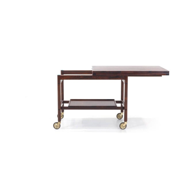 Beautiful rosewood serving cart with removable bottom tray. The top slides to one side then opens to twice the size...