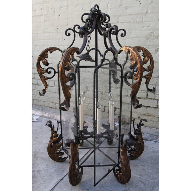 Monumental Spanish style hand wrought iron lantern with gold highlights. Glass sides and door for changing bulbs. Six...