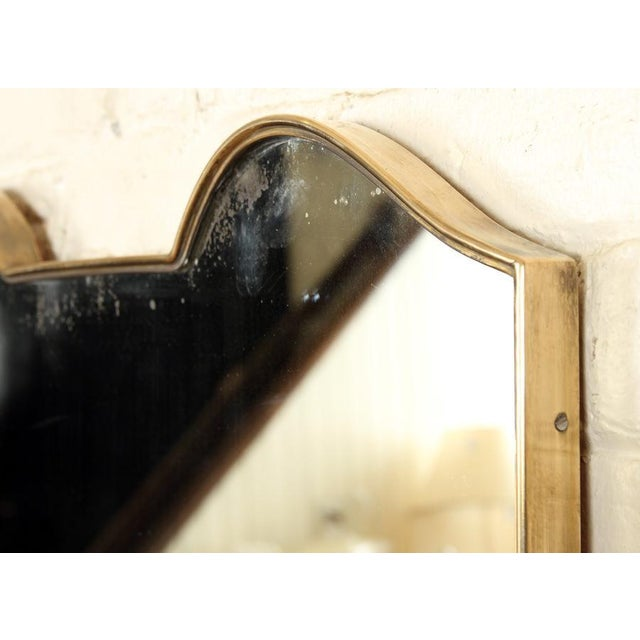 An Italian brass and glass shield form mirror circa 1950. Attributed to Gio Ponti. Beautiful exposed brass fasteners and...
