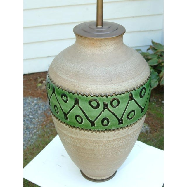 Natural pottery with a glazed decorative band. This piece would look great with an off white shade.