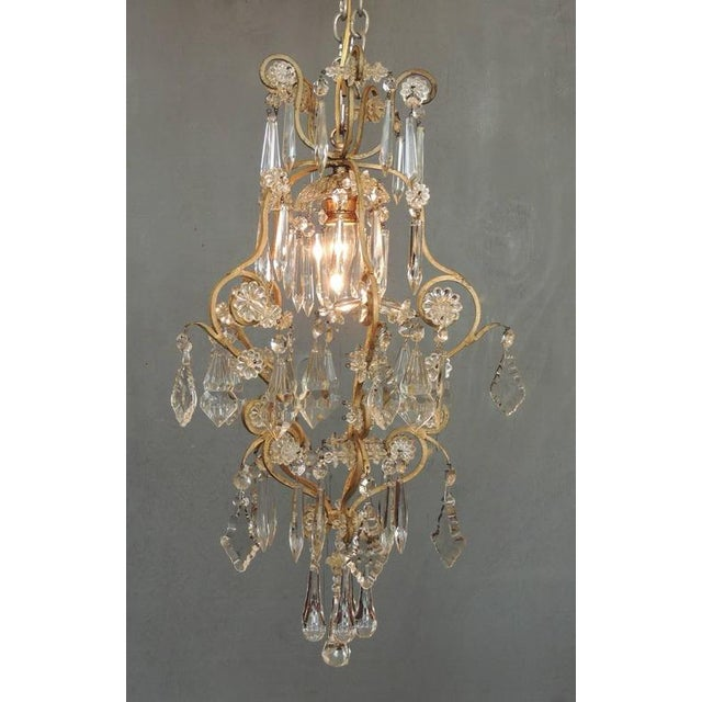 This small French Neoclassical brass and crystal chandelier lantern made in the first half of the 20th century, circa...