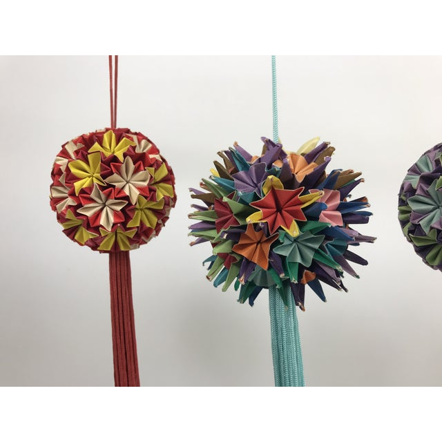 Set of four handmade origami round Christmas tree ornaments. There are two different techniques present both colorful with...