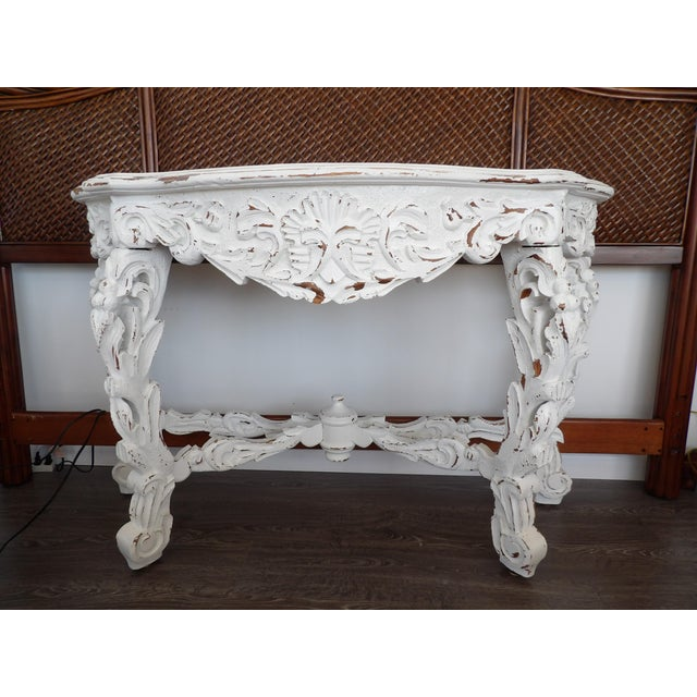 With exceptional hand carved details in the legs, skirt and supports, this is an amazing large console table. It has a...