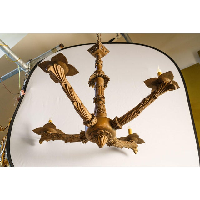Hand-carved giltwood chandelier, circa 1860-1880, France. Four arms with candelabra-size lights on later tole bobeche...