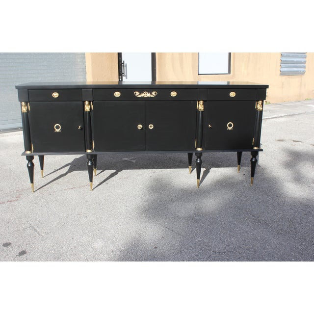 Long French Empire style antique sideboard or buffet made of mahogany, the mahogany wood has been ebonized and finished...