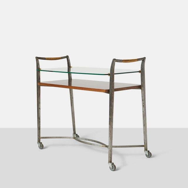 A rare and unique wrought-iron bar cart with brass details, a glass upper section, and mahogany shelf. By Dominique (Andre...