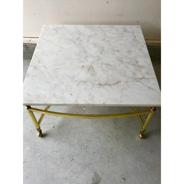 This vintage brass and marble coffee table is the perfect Hollywood Regency piece. Marble is Italian with tones of white,...