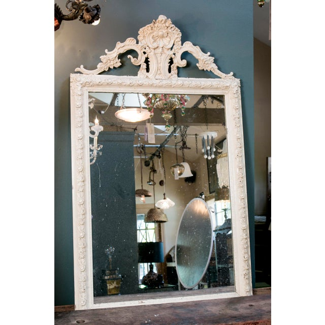 Beautiful, large antique Rococo-style French mirror with floral motif, circa 1900. Carved tassels line the base of the...
