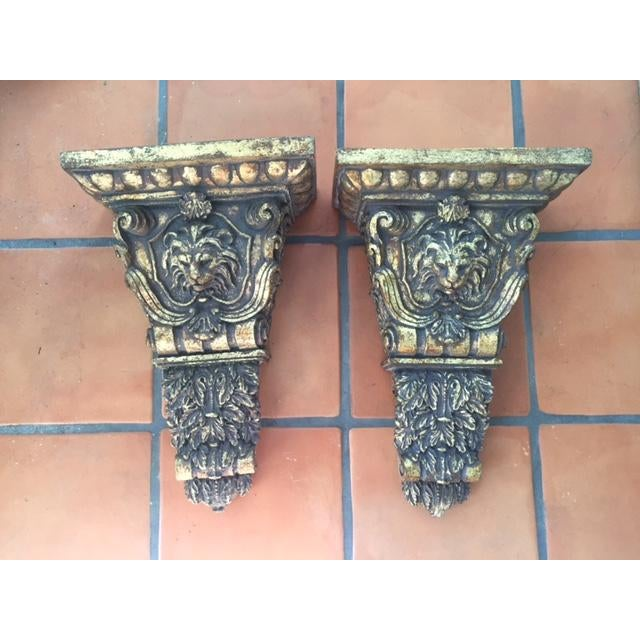 Substantial pair of lion head sconces/wall brackets. Made of heavy resin/plaster with lovely gold distressed finish. Could...