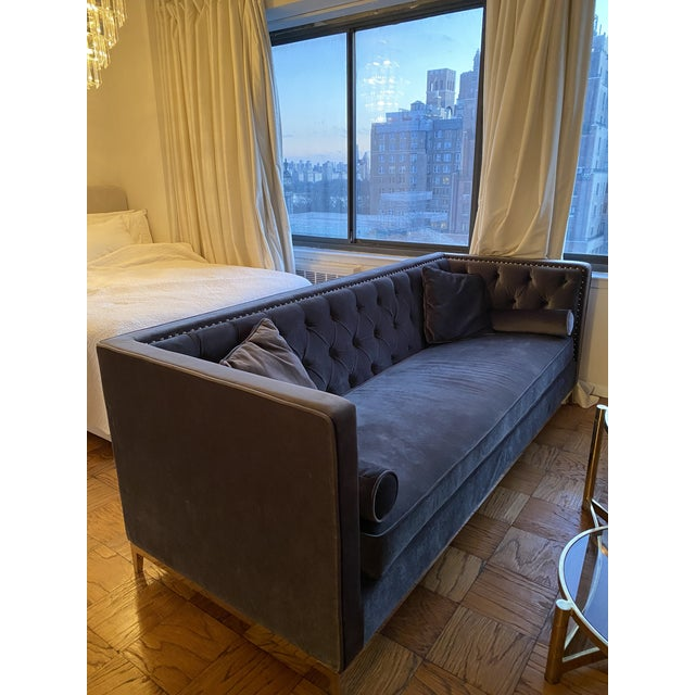 Modern charcoal grey chesterfield sofa with throw pillows, and chrome accents.