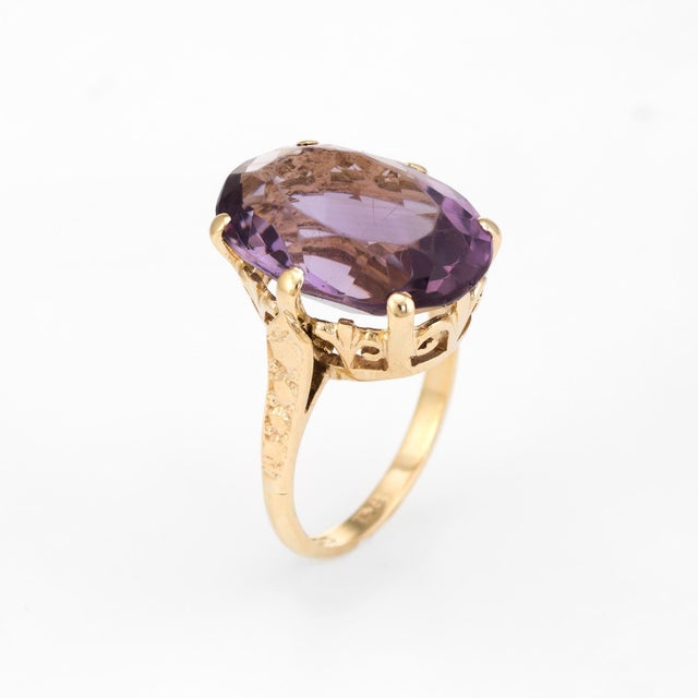 Circa 1972, a finely detailed vintage cocktail ring is crafted in 9 karat yellow gold. The large faceted oval cut amethyst...