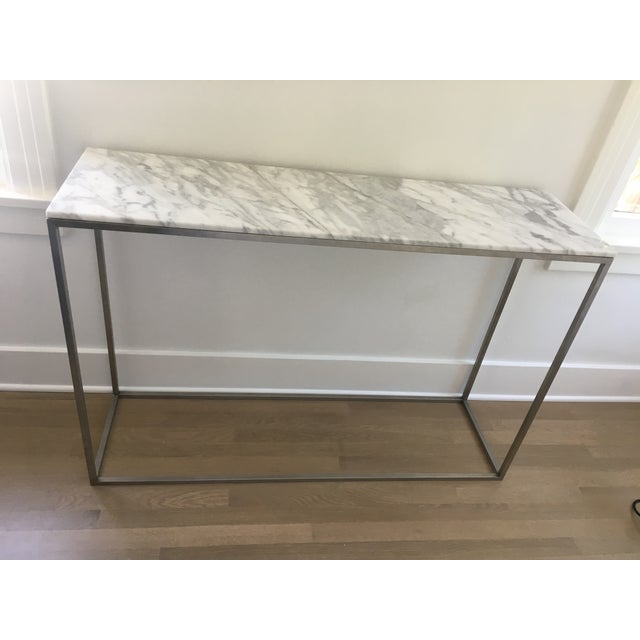 "From DWR, a Rubik console table made of brushed stainless steel and a solid Arabescato marble top. Dimensions: H 32"" W 48""..."