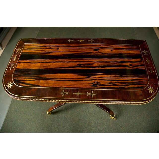 """An English Regency rosewood and calamander brass inlaid ormolu mounted games table with patented """"lazy tongs"""" action in..."""