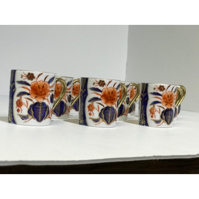20 piece contemporary porcelain cups and saucers decorated in the Imari palette with gold accents throughout the designs....