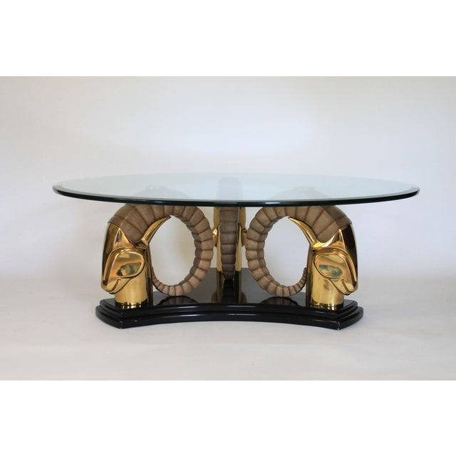 Highly detailed brass rams head coffee table. Thick circular glass top with beveled edge. Sculptural high gloss black...