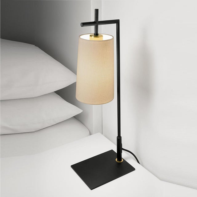 Satin black lamp with brushed bronze and a tapered shade. The tapered shade is suspended and gives good down light....