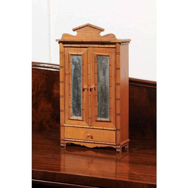 19th Century French miniature armoire or wardrobe made from faux bamboo with a pair of mirrored doors and one drawer. The...