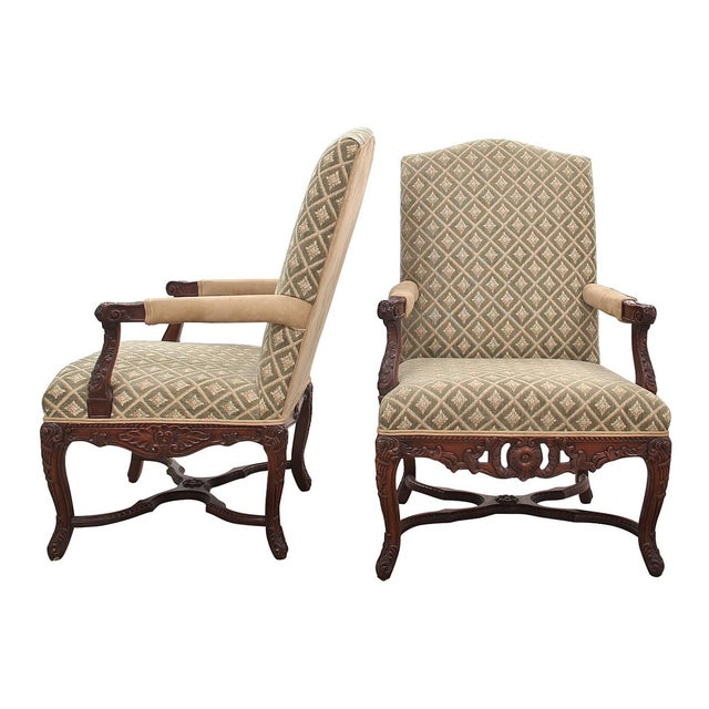 A pair of ornately carved Italian style armchairs. Seat cushions are upholstered in a woven cut pile fabric with a diamond...