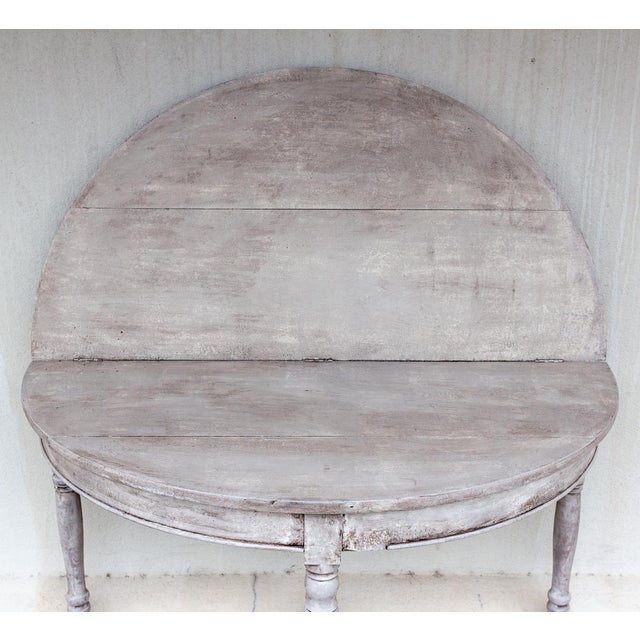 This wonderfully functional demi-lune console table unfolds to reveal a generously sized round table that has been hand-...
