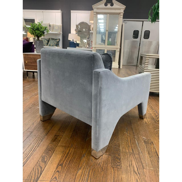 A which and quintessentially comfortable lounge chair crafted from luxe velvet upholstery and polished, stainless steel...