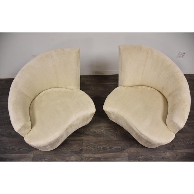 A pair of modern Bilbao half swivel lounge chairs designed by Vladimir Kagan with an off white tweed - like fabric. Seat...