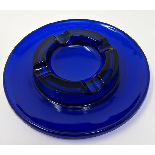 """This 1950s cobalt blue glass ashtray is perfect for yesteryear and today. Measuring in a 7"""" round around with four cutouts..."""