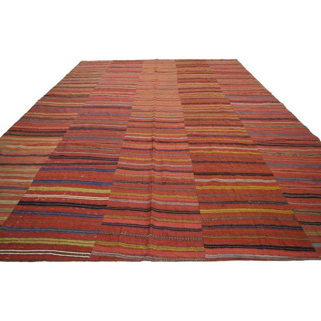 This handwoven wool Turkish kilim Jajim kilim rug features a variety of colorful stripes composed of both wide and narrow...